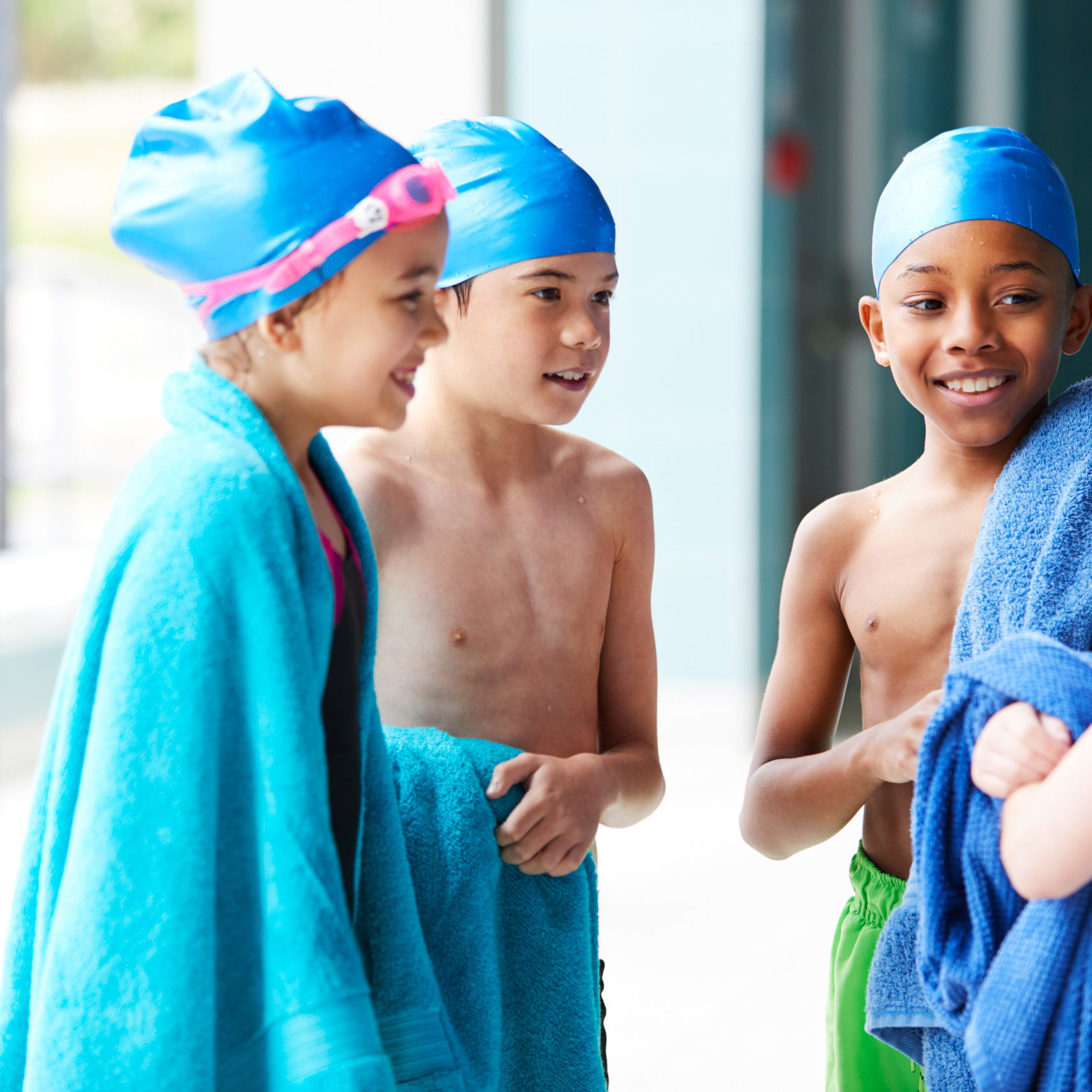 Group Of Children Wearing Towels On Edge Of Swimming Pool After Lesson
